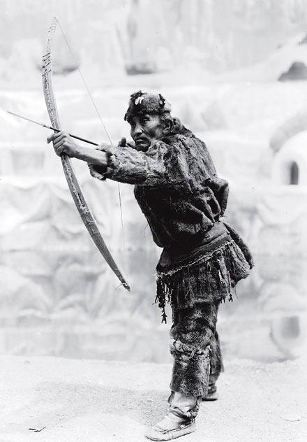 Рис. 14.2. Эскимос демонстрирует лук и стрелу с наконечником из слоновой кости на выставке в Чикаго в 1893 году. Археологи часто употребляют этнографическое наименование, такое как наконечник стрелы, предполагая, что их артефакт идентичен наконечникам стрел и, соответственно использовался теми людьми, которые изготовили артефакт. Это простой пример археологической аналогии