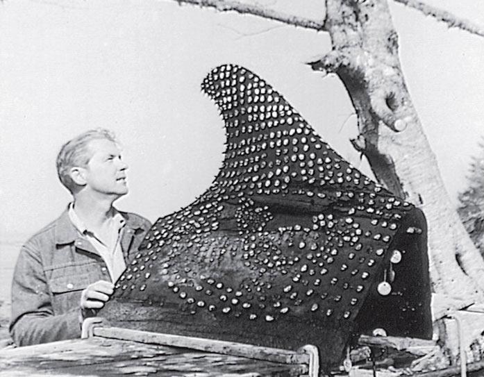 Рис. 11.17. Плавник кита, вырезанный из дерева кедра, и украшенный более чем семью сотнями зубов морской выдры, найденный в Озетте, штат Вашингтон. Зубы в нижней части изображают мифическую птицу с китом в когтях