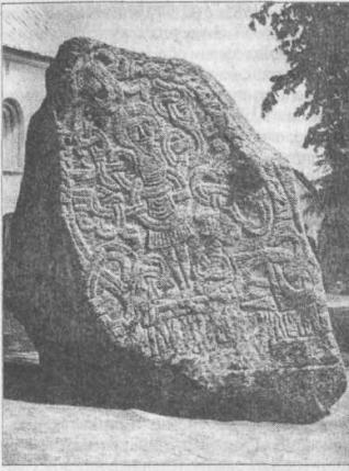 Рис. 124. Еллингский камень Одна из сторон камня из Еллинге показывает сцену распятия. Христос окружен плетением, часть рунической надписи можно увидеть на основании камня. Около 980 г.