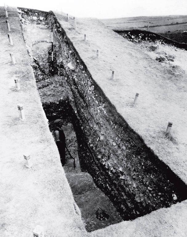 Рис. 9.4. Классический пример вертикального раскопа, сделанного экспедицией сэра Мортимера Уилера, в замке Мейден Касл в Дорсете, Англия, перед Второй мировой войной. Столбики по сторонам раскопа и рабочий в траншее дают представление о размерах раскопок