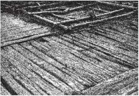 Рис. 12. Перекресток мостовых новгородских улиц на уровне слоя ХIII в. На заднем плане - нижние венцы жилого дома.