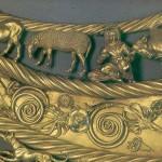 Толстая Могила, пектораль. По обе стороны от лошадей стоят две коровы, левую из которых сосет теленок (рис. 3.74), а правая – оглянулась на лежащего теленка. Далее за коровами скифы, левый из которых держит амфору, а правый – доит овцу.