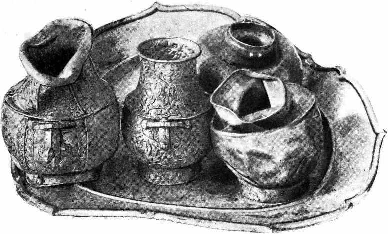 Рис. 11. Золотые сосуды, стоящие на серебряном блюде, найденные при раскопках тайника кургана № 2 в положении, показанном на фотографии.